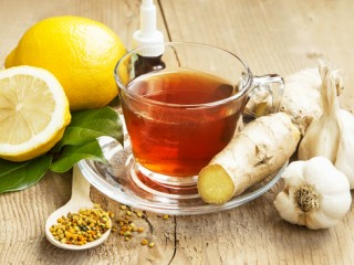 Fresh Lemon Tea in Transparent Cup with Ginger,Pollen and Garlic on Wooden Background.Natural Cold Remedy