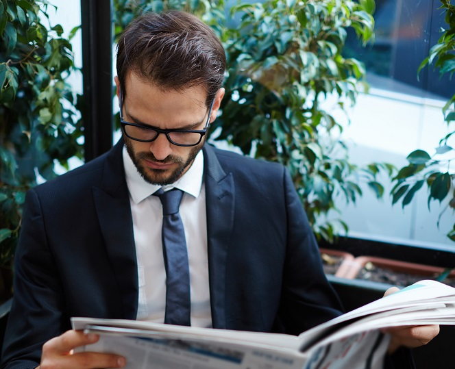 Portrait of young brunette hair businessman sitting in a coffee shop reading a newspaper looking concentrated, handsome business man holding open newspaper sitting in cafe