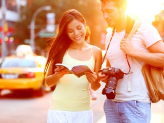 Travel tourist couple traveling in New York reading guide book standing with SLR camera at sunset on Manhattan with yellow taxi cab in the background. Happy young multiracial couple on summer holidays