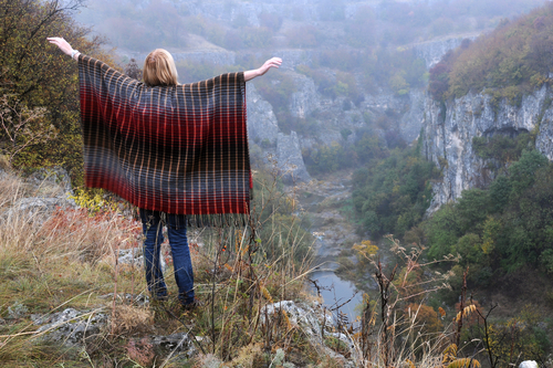 Caucasian lady stands on the edge of Emen canyon with her arms sideways near the city of Veliko Tarnovo in Bulgaria on a raw foggy morning in the fall