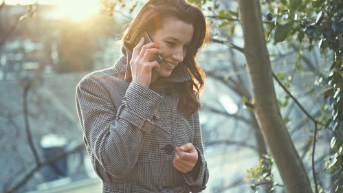 Businesswoman use her mobile phone outdoor in a small village - instagram style natural shot