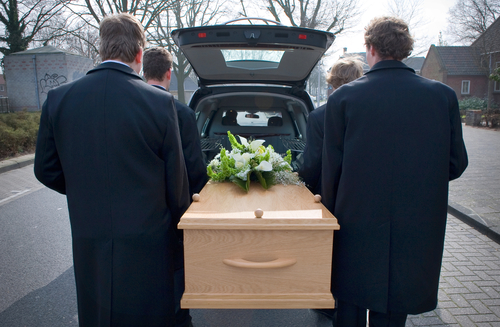 Bearers are carrying a coffin out of a mourning car