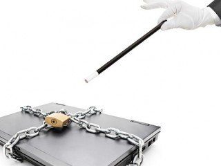 A magician holding a magic wand over a laptop with chain and padlock isolated on white background